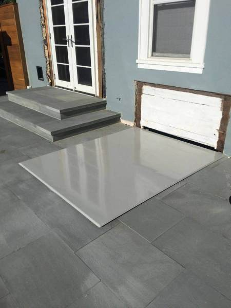 LuciGold lightweight all aluminum basement bulkhead door, flat profile hatch on stone patio